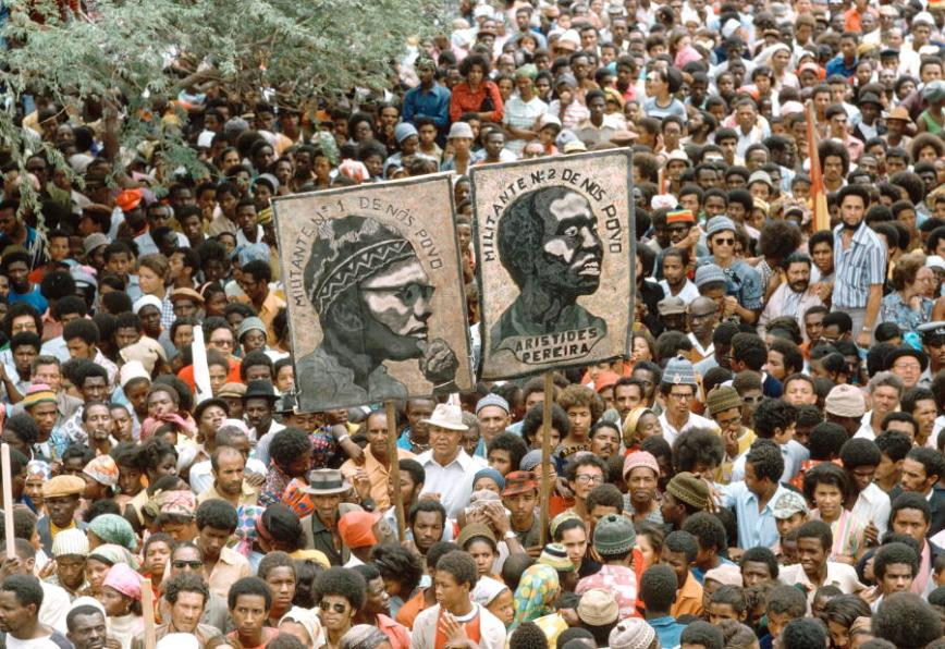 Cape Verdeans in large numbers gather in Praia, Santiago Island, to welcome a visit from PAIGC Secretary-General, Aristides Pereira, first President of independent Cape Verde.  A portrait of Amilcar Cabral,
