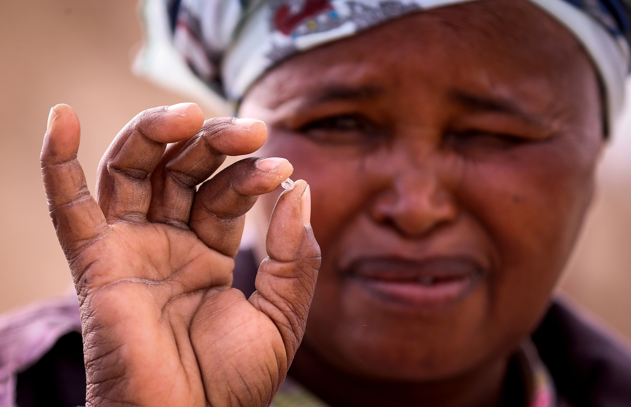 An artisanal miner holds an uncut diamond in her hand in Kimberley